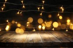 Ξύλινος πίνακας πινάκων μπροστά από τα θερμά χρυσά φω'τα γιρλαντών Χριστουγέννων στο ξύλινο αγροτικό υπόβαθρο Στοκ Φωτογραφία
