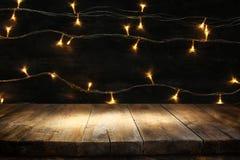 Ξύλινος πίνακας πινάκων μπροστά από τα θερμά χρυσά φω'τα γιρλαντών Χριστουγέννων στο ξύλινο αγροτικό υπόβαθρο Στοκ Εικόνα