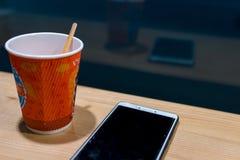 Ξύλινος πίνακας στον καφέ, νύχτα, σκοτεινό θέμα smartphone και τσάι, καφές έννοια να κουβεντιάσει, εργασία, που μαθαίνει on-line στοκ φωτογραφία