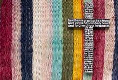 Ξύλινος σταυρός με την προσευχή Λόρδου ` s στο χρωματισμένο υπόβαθρο ταπήτων Στοκ Φωτογραφίες