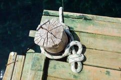 Ξύλινος στυλίσκος πρόσδεσης με το άσπρο σχοινί στο λιμενοβραχίονα Στοκ Εικόνες
