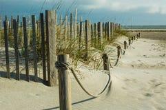 Ξύλινος φράκτης και φράκτης σχοινιών στην παραλία με τις βρώμες άμμου και καθισμάτων στοκ φωτογραφία με δικαίωμα ελεύθερης χρήσης