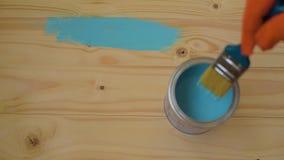 Ξύλινος φραγμός χρωμάτων χεριών με τη βούρτσα φιλμ μικρού μήκους