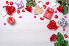 Ξύλινο άσπρο υπόβαθρο με τις κόκκινα καρδιές, τα δώρα και τα τριαντάφυλλα Στοκ εικόνα με δικαίωμα ελεύθερης χρήσης