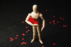 Ξύλινο άτομο με μια κόκκινη καρδιά στα χέρια του 14 Φεβρουαρίου, αγάπη και σχέσεις στοκ εικόνες