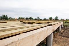 Ξύλινο ίδρυμα σπιτιών πλαισίων στους σωρούς βιδών, εργοτάξιο οικοδομής στοκ εικόνες