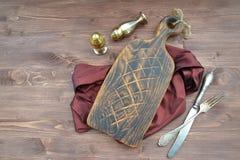 Ξύλινο αγροτικό υπόβαθρο Σκοτεινός καφετής τέμνων πίνακας με το ασημένια μαχαίρι και το δίκρανο Οργανική διατροφή στοκ εικόνα