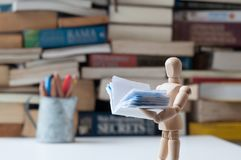 Ξύλινο ανδρείκελο που διαβάζει το μικροσκοπικό βιβλίο Στοκ εικόνα με δικαίωμα ελεύθερης χρήσης