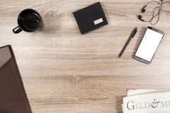 Ξύλινο γραφείο με το smartphone, ακουστικά, μάνδρα, πορτοφόλι, κούπα καφέ στοκ εικόνες