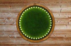 Ξύλινο ελαφρύ πλαίσιο δαχτυλιδιών με το πράσινο σκηνικό χλόης στοκ εικόνα