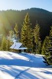 Ξύλινο εξοχικό σπίτι σε έναν χιονώδη χορτοτάπητα Στοκ Εικόνες