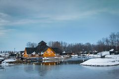 Ξύλινο εστιατόριο κοντά στην παγωμένη λίμνη στο ηλιοβασίλεμα, χειμερινή νεφελώδης ημέρα στοκ φωτογραφία με δικαίωμα ελεύθερης χρήσης