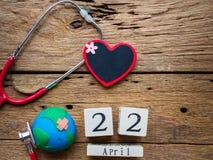 Ξύλινο ημερολόγιο φραγμών για την παγκόσμια γη ημέρα στις 22 Απριλίου, στηθοσκόπιο στοκ εικόνες