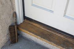Ξύλινο κατώφλι, πόρτα και συγκεκριμένη προσγείωση ενός σπιτιού με μια παλαιά βούρτσα παπουτσιών στη γωνία Στοκ εικόνες με δικαίωμα ελεύθερης χρήσης