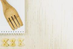 Ξύλινο κουτάλι και ξηρά πεταλούδα νουντλς στοκ εικόνες