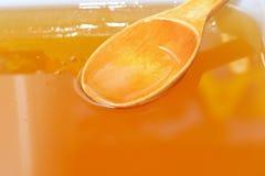 Ξύλινο κουτάλι στο φρέσκο υγρό μέλι στοκ φωτογραφίες