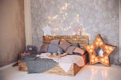 Ξύλινο κρεβάτι στην κρεβατοκάμαρα με τα όμορφα διακοσμητικά στοιχεία και μια καμμένος γιρλάντα Στοκ Φωτογραφίες