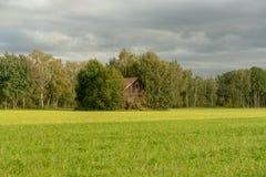 Ξύλινο κτήριο από έναν πράσινο τομέα στοκ φωτογραφία με δικαίωμα ελεύθερης χρήσης