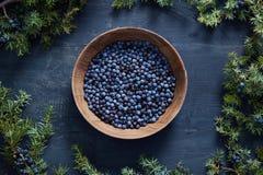 Ξύλινο κύπελλο με τους σπόρους του ιουνιπέρου στοκ φωτογραφία