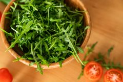 Ξύλινο κύπελλο του φρέσκου πράσινου, φυσικού arugula με τις ντομάτες κερασιών σε ένα ξύλινο υπόβαθρο Στοκ εικόνες με δικαίωμα ελεύθερης χρήσης