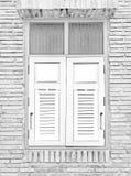Ξύλινο λευκό παραθυρόφυλλων παραθύρων σε ένα παραδοσιακό εξωτερικό πλινθοδομής Στοκ Εικόνα