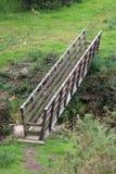 Ξύλινο μονοπάτι επαρχίας γεφυρών για πεζούς πέρα από το ρεύμα Στοκ φωτογραφία με δικαίωμα ελεύθερης χρήσης