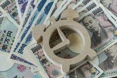 Ξύλινο ξυπνητήρι στο σωρό των ιαπωνικών τραπεζογραμματίων γεν ως χρονικό cou Στοκ Εικόνες