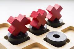 Ξύλινο παιχνίδι toe TAC σπασμού στο άσπρο υπόβαθρο Τρεις Ερυθροί Σταυροί ο στοκ εικόνες