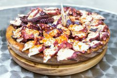Ξύλινο πιάτο του της Γαλικίας μαγειρευμένου ύφος χταποδιού με το ελαιόλαδο πάπρικας και gallega pulpo Λα Στοκ εικόνες με δικαίωμα ελεύθερης χρήσης