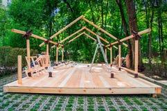 Ξύλινο πλαίσιο ενός νέου περίπτερου αγορών κάτω από την κατασκευή στην αγορά αγροτών Νέα κατασκευή στο υπόβαθρο του θερινού δάσου στοκ φωτογραφίες