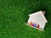 Ξύλινο πρότυπο σπιτιών που τοποθετείται σε έναν πράσινο χορτοτάπητα και μια ζωηρόχρωμη πώληση κειμένων στο σπίτι σύσταση σπιτιών  στοκ εικόνες
