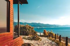 Ξύλινο σπίτι από το τέλειο ηλιοβασίλεμα άποψης τοπίων θάλασσας και βουνών Στοκ Εικόνα