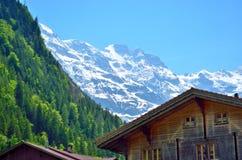 Ξύλινο σπίτι κάτω από το ελβετικό Apls στα βουνά στοκ εικόνα