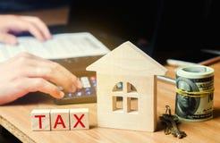 """Ξύλινο σπίτι με την επιγραφή """"φόρος """" Φόροι στην ακίνητη περιουσία, πληρωμή Ποινική ρήτρα, καθυστερούμενα Κατάλογος των φορολογού στοκ φωτογραφία με δικαίωμα ελεύθερης χρήσης"""