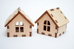 Ξύλινο σπίτι παιχνιδιών δύο σε ένα άσπρο υπόβαθρο, ένα σπίτι που ξετυλίγεται λοξά, η έννοια των σπιτιών για-πώλησης στοκ φωτογραφίες με δικαίωμα ελεύθερης χρήσης