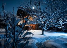 Ξύλινο σπίτι στη χειμερινή δασική νύχτα σεληνόφωτο Στοκ φωτογραφία με δικαίωμα ελεύθερης χρήσης