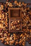 Ξύλινο σύνολο κιβωτίων των καρυδιών Μίγμα των φουντουκιών, των ξύλων καρυδιάς και των αμυγδάλων στον πίνακα, κάθετο πλαίσιο Στοκ Εικόνα