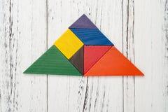 Ξύλινο τανγκράμ που διαμορφώνεται ως τρίγωνο στο άσπρο ξύλινο υπόβαθρ στοκ φωτογραφίες