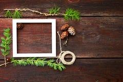 Ξύλινο υπόβαθρο Χριστουγέννων Κλάδοι και κώνοι του FIR με το άσπρο πλαίσιο για το copyspace Στοκ Φωτογραφίες