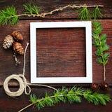 Ξύλινο υπόβαθρο Χριστουγέννων Κλάδοι και κώνοι του FIR με το άσπρο πλαίσιο για το copyspace Στοκ εικόνα με δικαίωμα ελεύθερης χρήσης