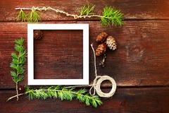 Ξύλινο υπόβαθρο Χριστουγέννων Κλάδοι και κώνοι του FIR με το άσπρο πλαίσιο για το copyspace Στοκ Φωτογραφία