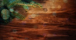 Ξύλινο υπόβαθρο Χριστουγέννων με τους κλάδους και τις σφαίρες έλατου στοκ εικόνα