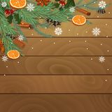 Ξύλινο υπόβαθρο Χριστουγέννων με τους κωνοφόρους κλάδους, τα πορτοκάλια και τα καρυκεύματα ελεύθερη απεικόνιση δικαιώματος