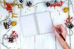 Ξύλινο υπόβαθρο Χριστουγέννων με τους κώνους και το σημειωματάριο Τα χέρια που γράφουν στο σημειωματάριο Στοκ Φωτογραφίες