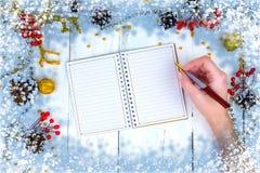 Ξύλινο υπόβαθρο Χριστουγέννων με τους κώνους και το σημειωματάριο Τα χέρια που γράφουν στο σημειωματάριο Στοκ Εικόνες