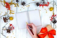Ξύλινο υπόβαθρο Χριστουγέννων με τους κώνους και το σημειωματάριο Τα χέρια που γράφουν στο σημειωματάριο Στοκ Φωτογραφία