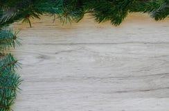 Ξύλινο υπόβαθρο Χριστουγέννων με το δέντρο έλατου Πλαίσιο διακοσμήσεων Χριστουγέννων στο ξύλινο υπόβαθρο Άποψη με το διάστημα αντ στοκ φωτογραφίες