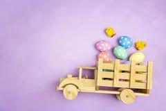Ξύλινο φορτηγό παιχνιδιών με τα αυγά και τα κοτόπουλα Πάσχας στην πλάτη στο PU Στοκ εικόνα με δικαίωμα ελεύθερης χρήσης