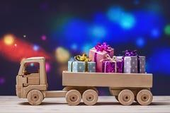 Ξύλινο φορτηγό παιχνιδιών στο εορταστικό υπόβαθρο με το διάστημα για το κείμενο ως ευχετήρια κάρτα Χριστουγέννων Στοκ Φωτογραφίες