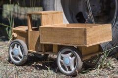 Ξύλινο φορτηγό παιχνιδιών στο υπόβαθρο της ρόδας ενός μεγάλου φορτηγού Στοκ Φωτογραφία